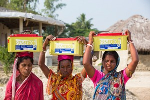Women carrying batteries home from the solar power charging station