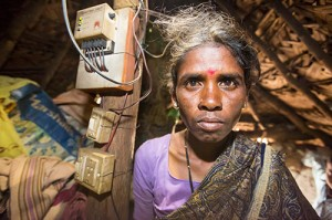 An untouchable woman in her hut, illuminated by an electric light, powered by an A4 sized solar panel